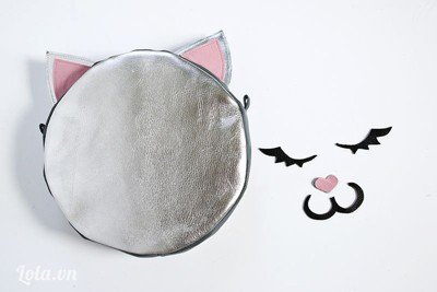 - Lộn chiếc túi ra mặt chính. Bạn cắt ra các miếng vải hình mắt, mũi và miệng mèo (như hình). Sau đó dùng keo dán vào mặt trước của túi. Cuối cùng bạn chỉ cần móc dây đeo cho túi là xong rồi!