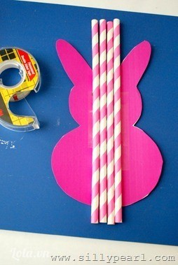 Dùng súng bắn keo đán các đoạn ống hút màu hồng lên tấm bìa cứng vừa cắt. Để dán được đều, nên bắt đầu dán từ phần giữa 2 tai thỏ.