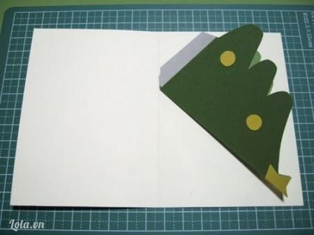 Các bạn lấy một tờ giấy bìa cứng, màu gì thì tuỳ các bạn. Rồi dán băng dính hai mặt vào phần đế ở phần gốc cây thông mà bạn gập vào ở phần trên, các bạn nhớ là mình dán băng dính một mặt ở phần đế còn một mặt là dán vào dấy bìa đấy nha!