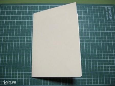 Gập đôi giấy bìa lại ( bên trong có hình cây thông ) rồi ấn xuống cho băng dính nó chắc.