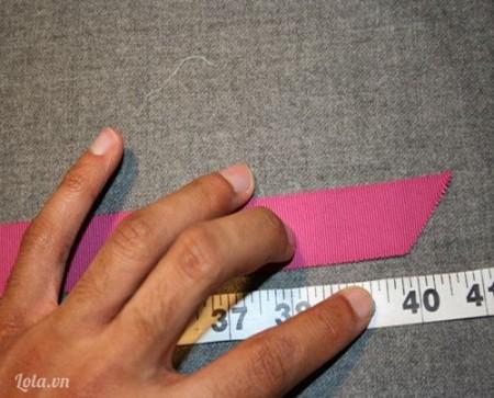 Cắt 1 dải ruy băng dài 40cm, sau đó cắt hai đường vạt chéo khoảng 45 độ ở hai đầu như hình bên.