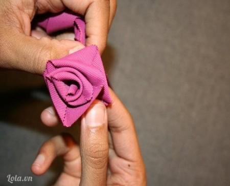 Trong khi giữ nếp gấp với bàn tay trái của bạn, dùng tay phải kéo đoạn băng dài ở phía dưới và xoắn cho đến khi đoạn băng bị cuốn chặt lại. Làm tương tự với từng lớp tiếp theo cho đến khi bạn thấy bông hoa bắt đầu hình thành.