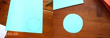 Bạn vẽ một hình tròn lên giấy bìa cứng , cắt hình tròn đó ra  kế tiếp đặt vòng tròn đã cắt dưới mặt đáy của lõi giấy đã dán giấy màu rồi bạn cố định chúng lại bằng keo dán.