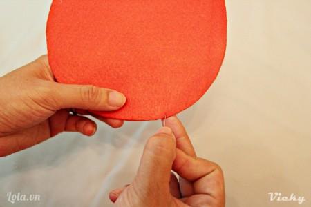 Đặt 2 mảnh vải nỉ đỏ chồng lên nhau, sau đó dùng kim may lại.