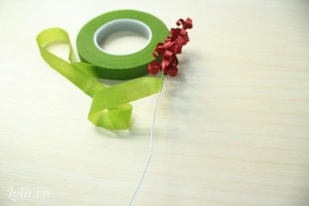 Sau khi quấn hết giấy màu đỏ, dùng băng keo màu xanh quấn tiếp theo để làm cành hoa