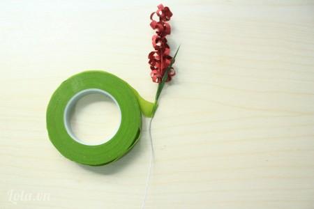 Vừa quấn băng keo xung quanh dây kẽm vừa đặt xen kẽ những mảnh giấy làm lá vào.