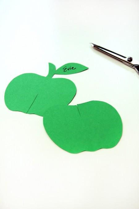 In mô hình quả táo ra giấy, sau đó bạn dùng bút chì vẽ họa tiết lên trên giấy màu cắt ra thành 2 miếng táo như trong hình