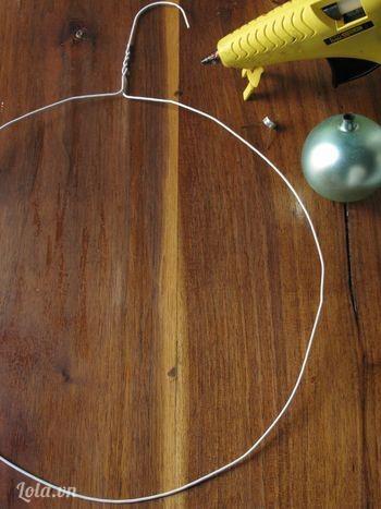 Uốn móc áo thành hình tròn, như một chiếc vòng treo. Nếu không thể tự làm được, bạn có thể nhờ người lớn hoặc người nào khỏe khỏe một tí hen! Không cần phải uốn thật đều đâu, chỉ cần tạo dáng cho móc áo thành hình tròn là được.