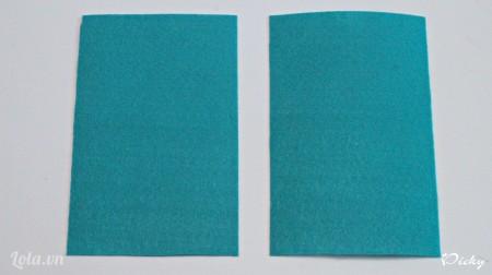Cắt vải nỉ màu xanh thành 2 mảnh hình chữ nhật bằng nhau.