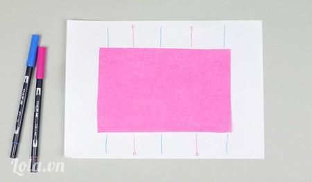 Đặt giấy màu lên trên tờ giấy trắng , vẽ các đường chia giấy như sau