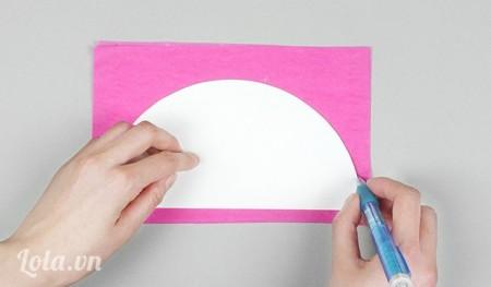 Đặt nữa vòng tròn lên trên sấp giấy màu vừa thoa keo, dùng viết vẽ hình nữa vòng tròn lên