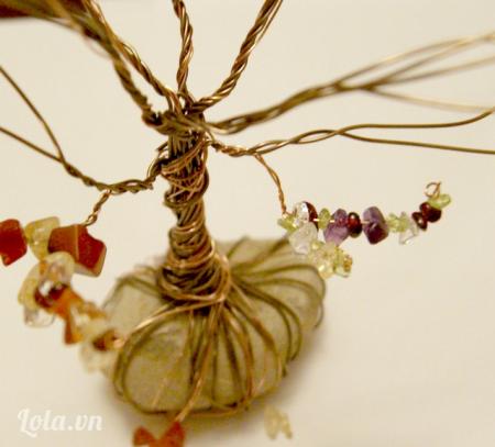 Lần lượt lấy hạt cườm xỏ qua các nhánh cành cây bằng dây đồng, xỏ đến đâu bạn đóng và xoắn dây đồng đến đó