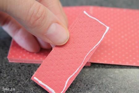 Tờ giấy đã cắt rìa lúc nãy. Bạn cắt đôi ra rồi quệt tí keo lên