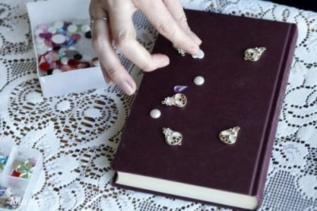 ướm những hạt cườm, nút, họa tiết lên trên bìa quyển sổ