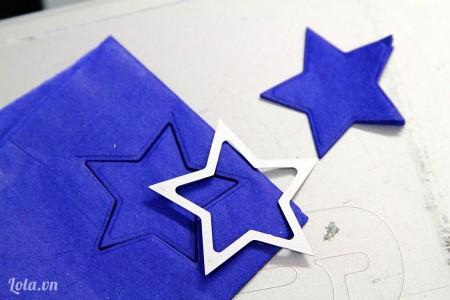 đặt mô hình ngôi sao ( làm sẵn từ giấy bìa) lên. Rồi cắt hình ngôi sao ra