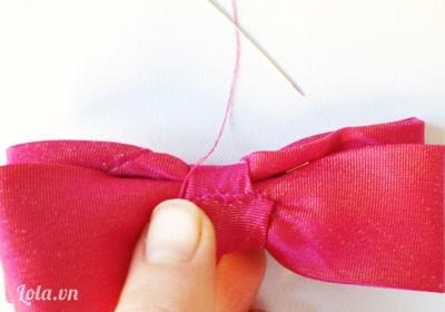 Rồi lấy dải nhỏ quấn quanh chỗ giữa nơ và khâu lại.