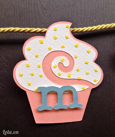 Dùng băng keo xốp dán chữ vào từng cupcake. Tada!!! Chúng ta đã có được một chiếc cupcake xinh xắn thế này đây. Bây giờ chỉ việc treo cupcake lên dây là chúng ta đã có một dây treo trang trí tiệc đầy năm cho bé, thật ngọt ngào nhưng không kém phần tinh tế phải không các bạn?