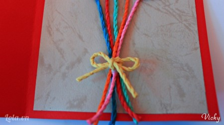 Dùng 1 sợi dây cói khác màu cột lại và thắt hình chiếc nơ. Sau đó dán cố định vào tấm thiệp.