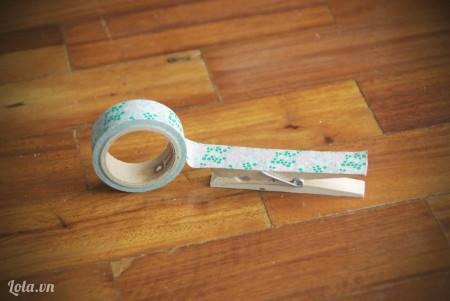 Bạn cắt băng dính bằng chiều dài của chiếc kẹp gỗ và dán chúng lên thân