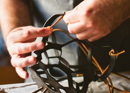 Cắt các sợi dây da để buộc vào thành trên của giỏ lưới, buộc túm lên cao làm dây treo, còn phần dưới đáy giỏ thì buông vài sợi tạo vẻ trữ tình. Bạn có thể dùng kìm bấm lỗ để tạo các lỗ hổng xỏ dây hoặc buộc trực tiếp đều được. Cắt các mẩu da nhỏ và bấm lỗ để xỏ vào trang trí cho dây da nếu thích.
