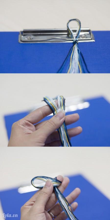 Thắt nút đầu chỉ thêu lại rồi dùng kẹp hồ sơ cố định đầu nút thắt.