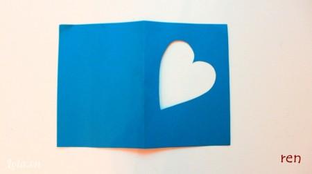 Dùng dao rọc giấy cắt một hình trái tim trên tấm giấy màu xanh.