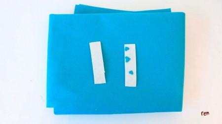 Cắt vải dạ màu trắng thành 2 mảnh hình chữ nhật có kích thước phù hợp với giường của bạn, cắt thêm những hình trái tim bằng vải màu xanh để trang trí.