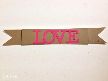 Sau khi đã hoàn tất việc sắp xếp trái tim lên khung, dùng giấy màu nổi cắt chữ Love và dùng giấy màu carton tạo hình băng rôn nhỏ xinh để làm nền cho chữ Love