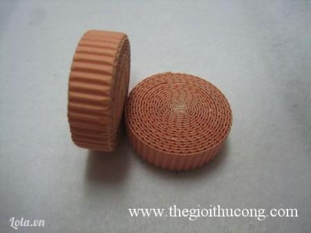 Làm thân và đầu chú heo :Đầu tiên bạn cắt 2 sợi giấy gợn sóng có kích thước 1cm* 1m Sau đó bạn cuộn tròn chúng lại ( lưu ý : bạn phải cuộn thật chặt tay, không lỏng lẻo )Sau đó dán mối bằng keo dán