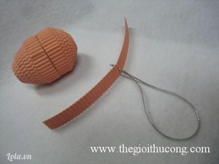 Ráp 2 phần đầu và thân chú heo dính vào nhau. Sau đó cắt 1 đọan giấy 1cm còn chiều dài bằng đường kính của vòng thân. Gấp đôi vào, cắt 1 lỗ nhỏ và xỏ dây qua