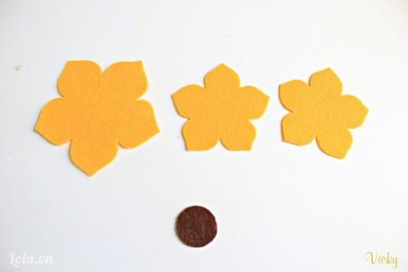 Cắt vải nỉ màu vàng thành 3 mảnh hình bông hoa và 1 mảnh hình tròn nhỏ màu nâu.
