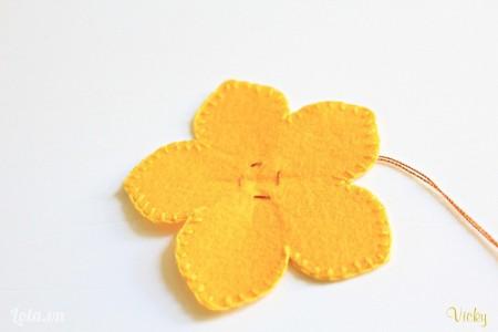 Các bạn may 1 đường chỉ thưa theo vòng tròn bên trong bông hoa như hình bên.