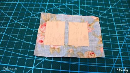 Dán 2 mảnh giấy bìa cứng vào mảnh vải. Chú ý chừa 1 đoạn nhỏ làm gáy sách.