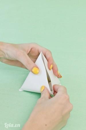 Giữ và ép hai bên giấy tạo thình hình như chiếc bánh ú