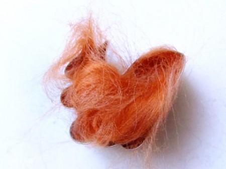 Đặt khuôn hình chú sóc lên trên miếng mút xốp, sau đó nhồi len vào bên trong khuôn như hình bên.