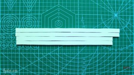 Cắt 4 thanh chữ nhật bằng giấy mô hình có kích thước phù hợp với bức tranh để làm viền.