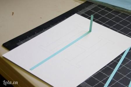 Đặt cái mảnh giấy nhỏ lên hình vừa in đo kích thước rồi gập nhẹ để lấy dấu