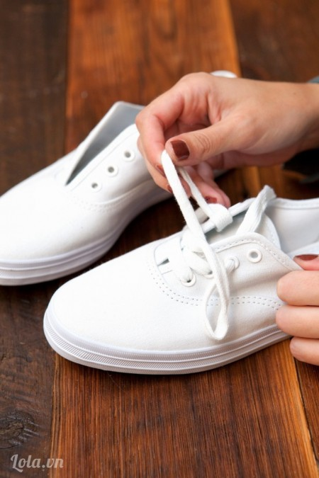 Tháo hết dây buộc của đôi giày ra như hình