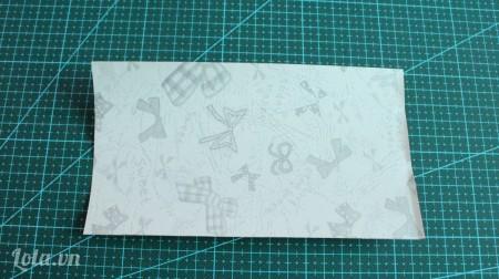 Cắt giấy hoa thành 1 mảnh hình chữ nhật, sao cho vừa đủ bao xung quanh lõi khăn giấy.