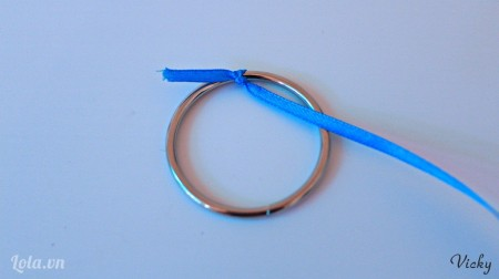 Cột cố định 1 đầu dây ruy băng vào vòng kim loại.