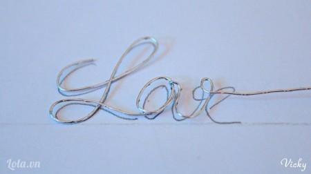 Vẽ chữ Love hoặc bất cứ chữ nào bạn thích lên giấy trắng. Sau đó uốn dây kẽm theo chữ đã vẽ.