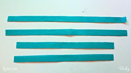 Cắt vải nỉ màu xanh thành 4 mảnh dài.