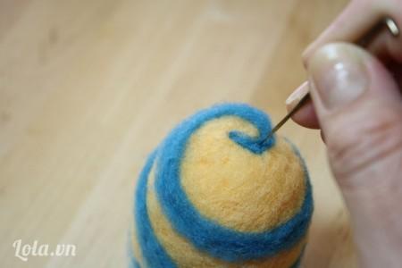 Dùng sợi len màu xanh quấn theo hình xoắn ốc sung quanh quả trứng. Sau đó dùng kim chọc để kết dính chúng với nhau là hoàn thành nhé.