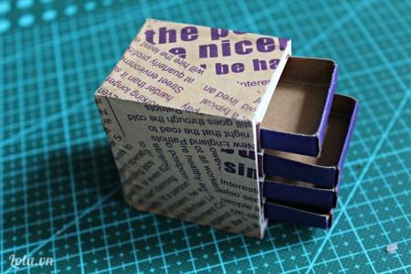 Giờ thì dùng giấy báo cũ hoặc giấy hoa bọc xung quanh tủ nhé! Sau khi bọc các bạn gắn các ruột hộp diêm vào để làm các ngăn tủ.