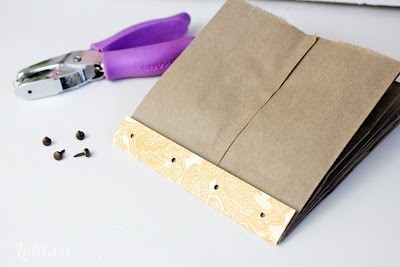 Dùng dụng cụ bấm lỗ đục 4 lỗ lên bìa giấy hoa văn. Kế tiếp đặt tờ giấy lên quyển sách dùng bút đánh dấu và đục lỗ xuyên qua quyển sách