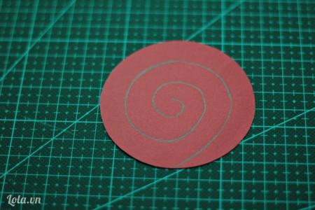 Dùng bút chì vẽ hình xoắn ốc bên trong hình tròn như hình bên.