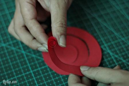 Cuộn tròn giấy theo chiều từ ngoài vào trong như hình.