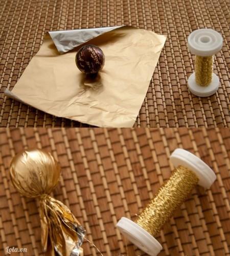 Cắt giấy gói keo thành hình vuông, đặt viên kẹo chocolate vào giữa tấm giấy, dùng sợi chỉ cột quanh giấy bao quanh bên ngoài viên kẹo.