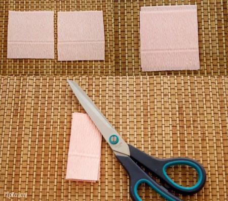 Cắt giấy nhún màu hồng thành 2 hình vuông có cạnh dài gấp 3 đường kính viên kẹo chocolate. Đặt 2 hình vuông chồng lên nhau, gấp đôi hình vuông theo chiều dọc.