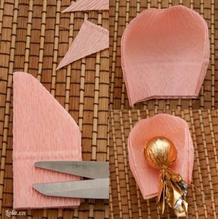 Dùng kéo cắt đường chéo hơi cung tròn cho nửa phần trên của phần giấy vừa gấp. Nhẹ nhàng lấy tay kéo phần cành hoa giãn qua hai bên tạo độ cong tròn tự nhiên cho cánh hoa. Tiếp theo đặt viên kẹo đã bọc giấy vào trong cánh hoa.